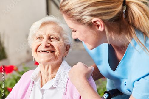 Fotografie, Obraz Altenpflegerin kümmert sich um Senior Frau
