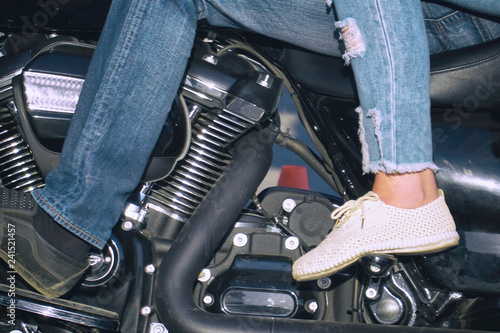 Men's and women's feet on motorcycle footboard