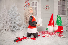 Pretty New Year Blonde Girl Posing In Black Latex Catsuit And Red Funny Christmas Dress On Background Of Her White Home With Snow And Trees
