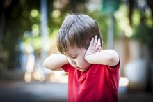 A 4 Year Old Autistic Child In A Red Shirt Closing His Ears With Hands As If Protecting From Noise. Autism Concept, Asperger Syndrome, Loud Noise, Scared Little Kid, Parents Divorce Trauma