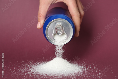 Fototapeta Woman pouring sugar from can on color background obraz