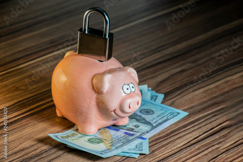 Fotografía  piggy bank on which there is a closed door lock as a symbol of a locked account