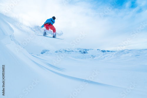 Snowboarder jumping from the rock