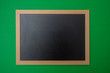 Black blank empty blackboard with wooden frame, green wall background, copy space