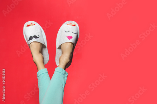 Obraz Cute funny couple on pink red. Woman wearing bright pants lying with legs upwards wearing unusual slippers with faces of man and woman - fototapety do salonu
