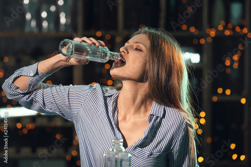 Fototapeta Young woman drinking alcohol in bar obraz na płótnie