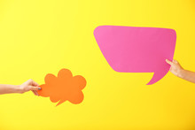 Female Hands With Blank Speech Bubbles On Color Background