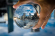 Leinwanddruck Bild - Cityscape photography in a clear glass crystal ball with dramatic clouds sky.