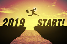 Silhouette Of Business Man Jump Between Cliff. Keep Go On To Success Concept At 2019 START Over A Beautiful High View Sunrise Sea Background. Ready In 2019 Years. GO TO 2019 YEAR CONCEPT