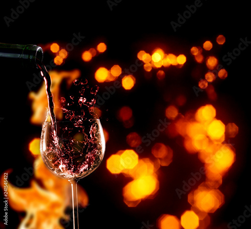 Pour in red wine, wine bottle and wineglass in front of fire