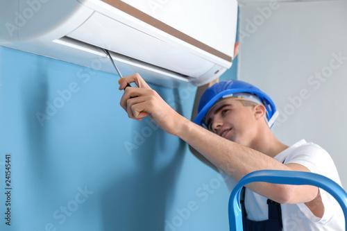 Male technician repairing air conditioner indoors