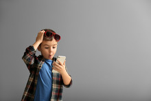 Emotional Little Boy Playing With Smartphone On Grey Background