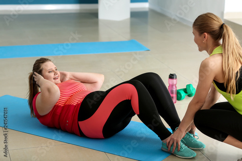 Beautiful plus size girl training with coach in gym. Concept of body positivity