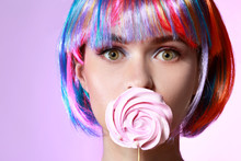 Beautiful Young Woman With Sweet Lollipop And Wig On Color Background