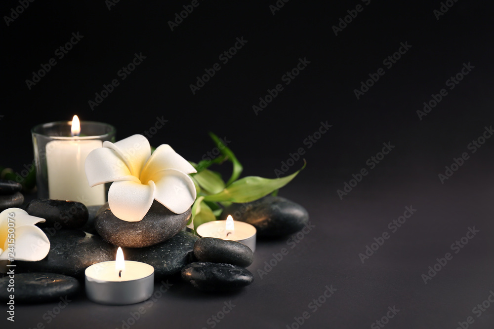 Fototapeta Beautiful spa composition with stones, candles and flowers on dark background
