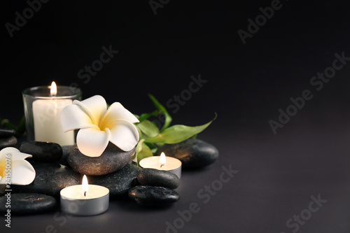 Beautiful spa composition with stones, candles and flowers on dark background