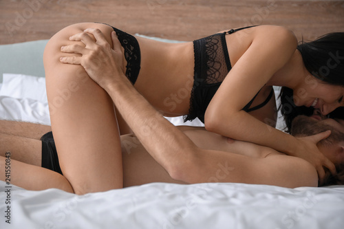 Passionate young couple on bed at home