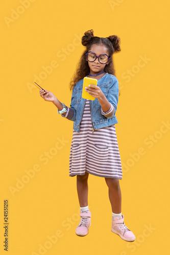 Fotografiet  Pleasant smart cute girl using her smartphone