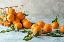 Overturned Basket With Tasty Juicy Tangerines On Light Table