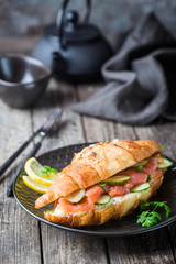 smoked salmon sandwich with cream cheese fresh and cucumbers on black plate