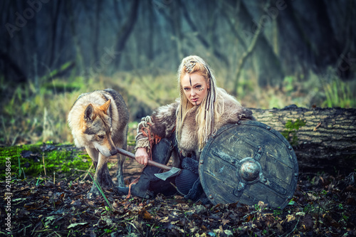 Photo  Viking warrior woman holding shield and ax  alone in woods with wolf next to her