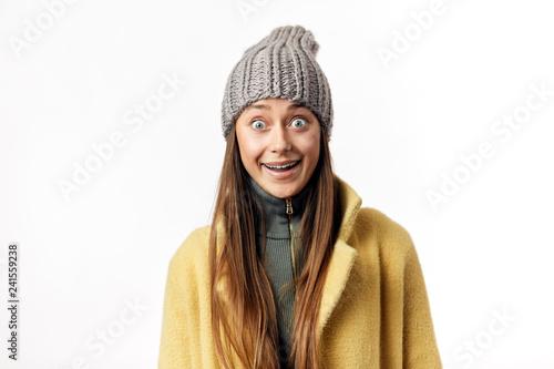 Studio Shot Of Happy Amazed Female With Big Round Eyes Dressed In
