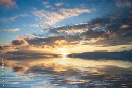 Obraz premium Wspaniały jasny zachód słońca nad spokojną powierzchnią morza.