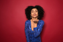 Portrait Of Young African-American Woman Blowing Kiss On Color Background