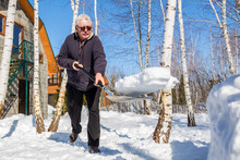 Senior Man Throwing Snow With Shovel From Private House Yard In Winter On Bright Sunny Day. Elderly Person Removing Snow In Garden After Heavy Snowfall. Physical Activity For People Outdoors