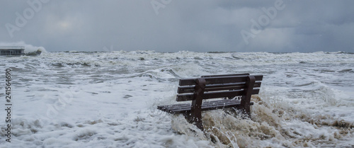 Leinwand Poster STORM AT SEA - A bench flooded by storm waves on a sea beach in Kolobrzeg