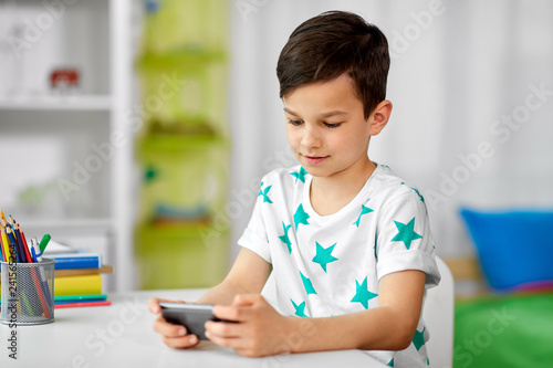 people, technology and communication concept - happy smiling boy with smartphone at home