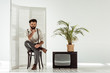 handsome bearded man sitting on chair near folding screen and tv in white room