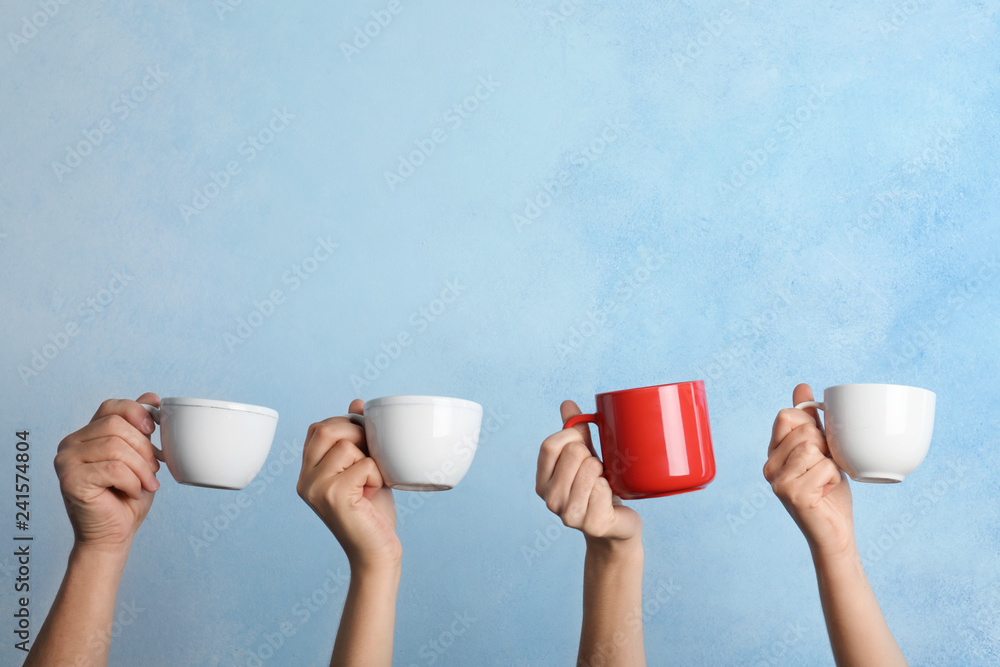 Fototapety, obrazy: Woman holding different cup from others on color background