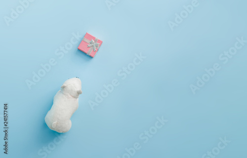 Polar bear toy with Christmas gift box on bright pastel blue background. Christmas and winter holidays concept.