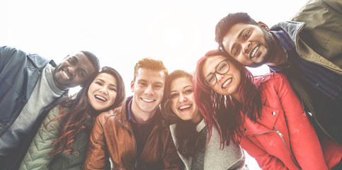 Happy friends from diverse cultures and races taking selfie photo - Main focus on right guys