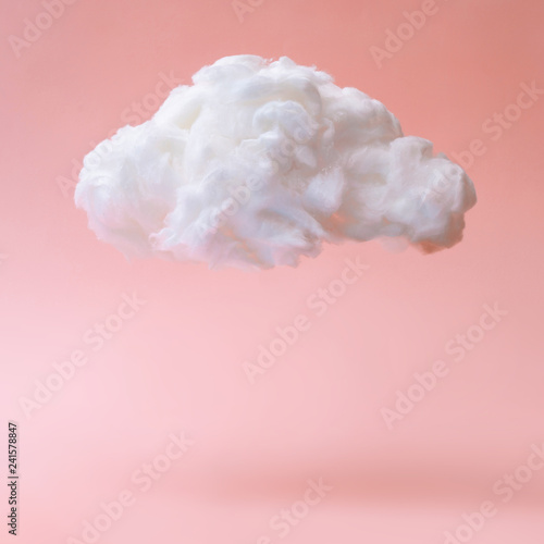 White cloud against pastel coral color background. Weather minimal concept.