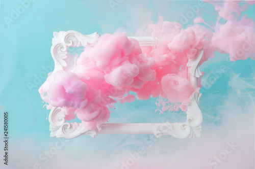 Obraz White vintage frame on pastel blue background with abstract pink cloud shapes. Minimal border composition. - fototapety do salonu