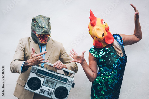 Foto op Plexiglas Carnaval Crazy senior couple dancing for new year's eve party wearing t-rex and chicken mask