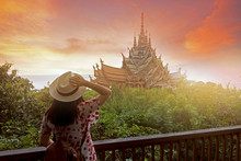 Woman Tourist Is Sightseeing Inside The Sanctuary Of Truth In Pattaya, Thailand During Sunset Summer Time.