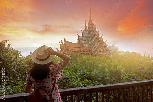 Valokuva  Woman tourist is sightseeing inside the Sanctuary of truth in Pattaya, Thailand during sunset summer time