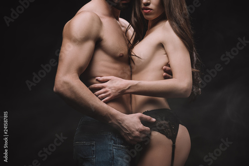 Photo  cropped view of boyfriend hugging nude girlfriend, isolated on black