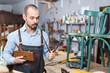 Restorer holding tools in woodwork studio