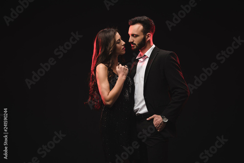 Fotografia sexual couple in black dress and tuxedo isolated on black