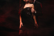 Cropped View Of Boyfriend Hugging Sensual Girl In Red Smoky Room