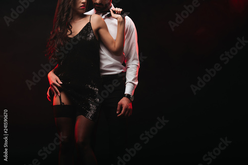 Fotografia  cropped view of passionate couple hugging isolated on black