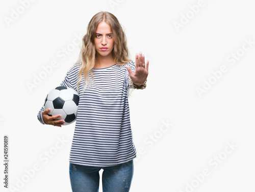 f8b3de805 Beautiful young blonde woman holding soccer football ball over isolated  background with open hand doing stop