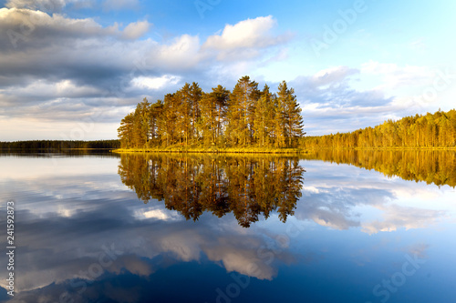 Beautiful volumetric clouds on a sunny day over a quiet forest lake