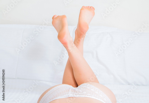 Sexy girl lying on the bed, legs raised up, part of the body, erotic boudoir concept