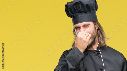 Fotografie, Tablou  Young handsome cook man with long hair over isolated background smelling something stinky and disgusting, intolerable smell, holding breath with fingers on nose
