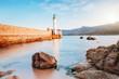 Leuchtturm am Meer am Ufer mit Bergen beim Sonnenuntergang